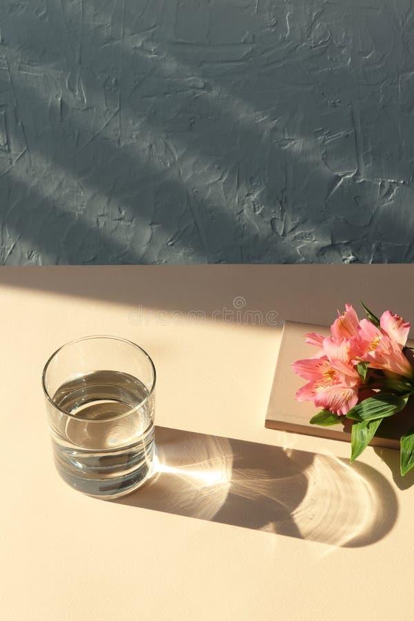 Λουλούδια, σημειώσεις, ποτήρι του νερού στον μπεζ πίνακα με τη σκιά στοκ φωτογραφίες