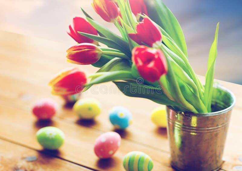 Λουλούδια τουλιπών στον κάδο και αυγά Πάσχας στον πίνακα στοκ εικόνες
