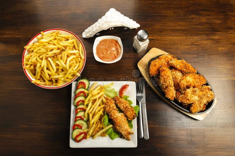 Λουρίδες και τηγανητά κοτόπουλου στοκ εικόνα
