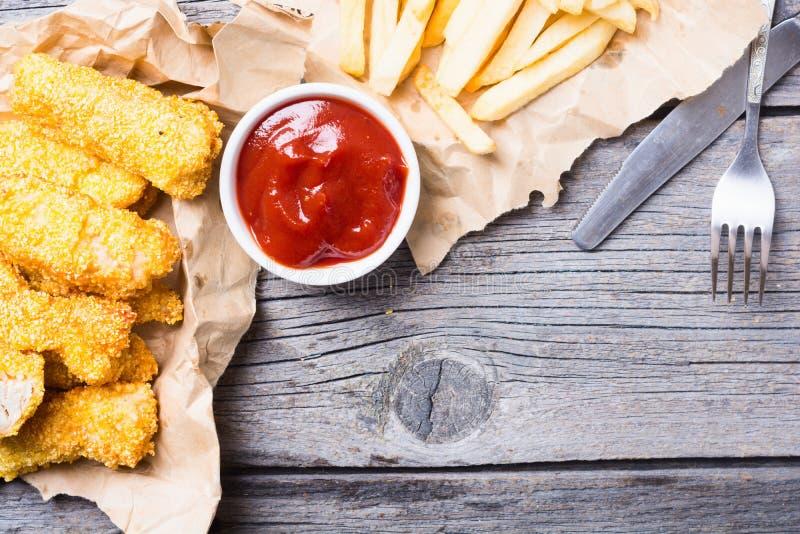 Λουρίδες και τηγανιτές πατάτες κοτόπουλου στοκ εικόνες με δικαίωμα ελεύθερης χρήσης