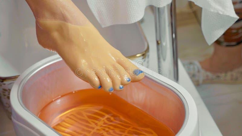 Λουτρό κεριών για τα πόδια beauty spa στο σαλόνι, κινηματογράφηση σε πρώτο πλάνο στοκ εικόνες