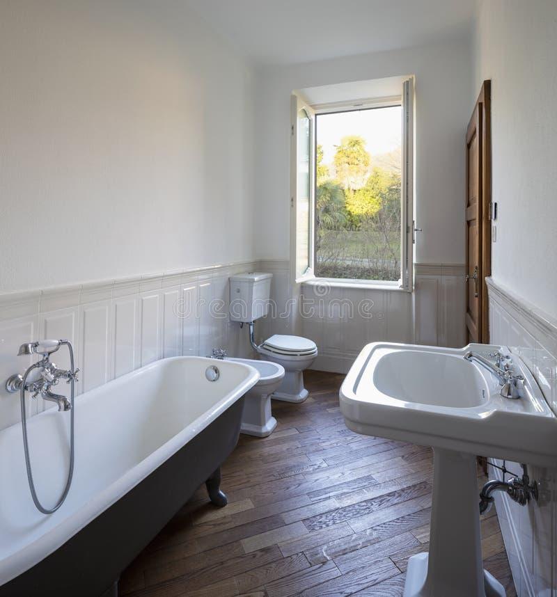 Λουτρό με τους άσπρους τοίχους και τη μεγάλη μαύρη μπανιέρα στοκ εικόνα