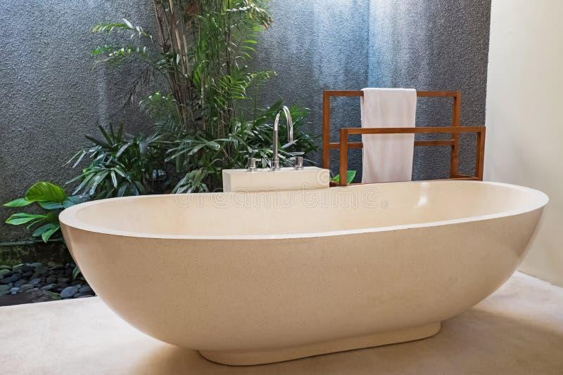 Λουτρό πολυτέλειας με την μπανιέρα πετρών και έννοια ανοιχτού χώρου σε ένα σύγχρονο σπίτι στοκ εικόνα με δικαίωμα ελεύθερης χρήσης