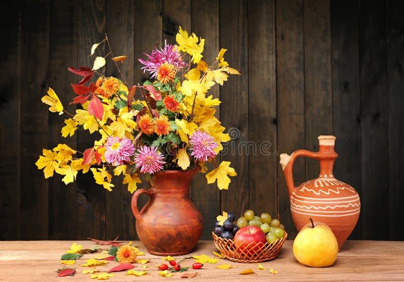 Λουλούδια και φύλλα σε ένα κεραμικό βάζο, φρούτα στοκ εικόνες