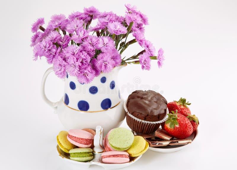 Λουλούδια στο βάζο με macaroons στο πιατάκι Γαρίφαλα και γλυκά στοκ φωτογραφία με δικαίωμα ελεύθερης χρήσης