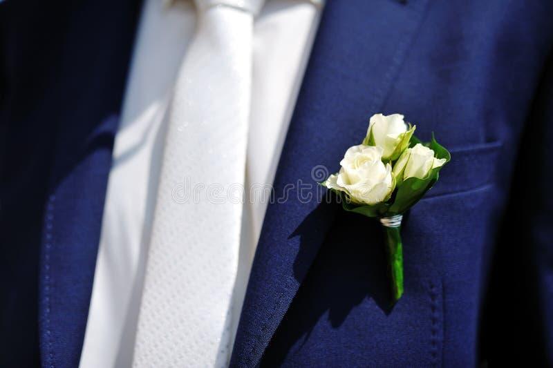 Λουλούδι μπουτονιέρων στο σακάκι του γαμήλιου νεόνυμφου στοκ εικόνες με δικαίωμα ελεύθερης χρήσης
