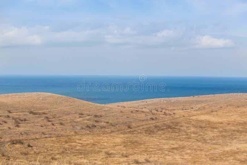 Λοφώδης ακτή και μια μπλε επιφάνεια της θάλασσας στοκ φωτογραφία με δικαίωμα ελεύθερης χρήσης