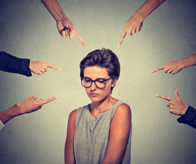 Λυπημένη αμήχανη γυναίκα στα γυαλιά που εξετάζει κάτω από πολλά δάχτυλα που δείχνουν την στοκ φωτογραφία