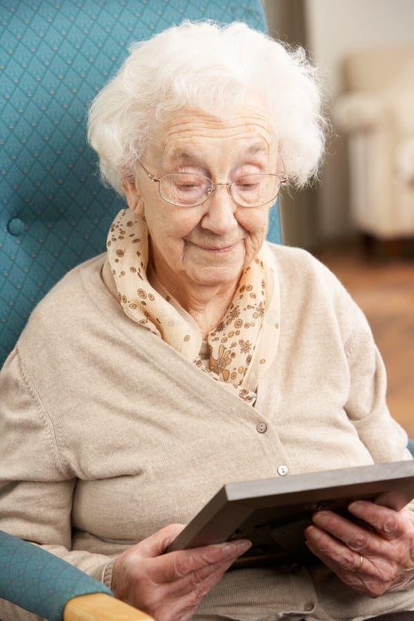 Λυπημένη ανώτερη γυναίκα που εξετάζει τη φωτογραφία στοκ εικόνες