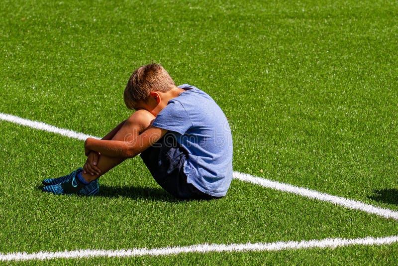 Λυπημένη απογοητευμένη συνεδρίαση αγοριών στη χλόη στο στάδιο στοκ φωτογραφία με δικαίωμα ελεύθερης χρήσης