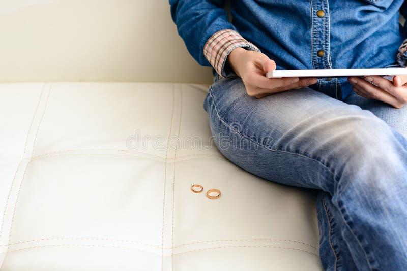 Λυπημένη γυναίκα μετά από το διαζύγιο, που εξετάζει μια οικογενειακή φωτογραφία στη συνεδρίαση πλαισίων στο πάτωμα κοντά στον καν στοκ εικόνες