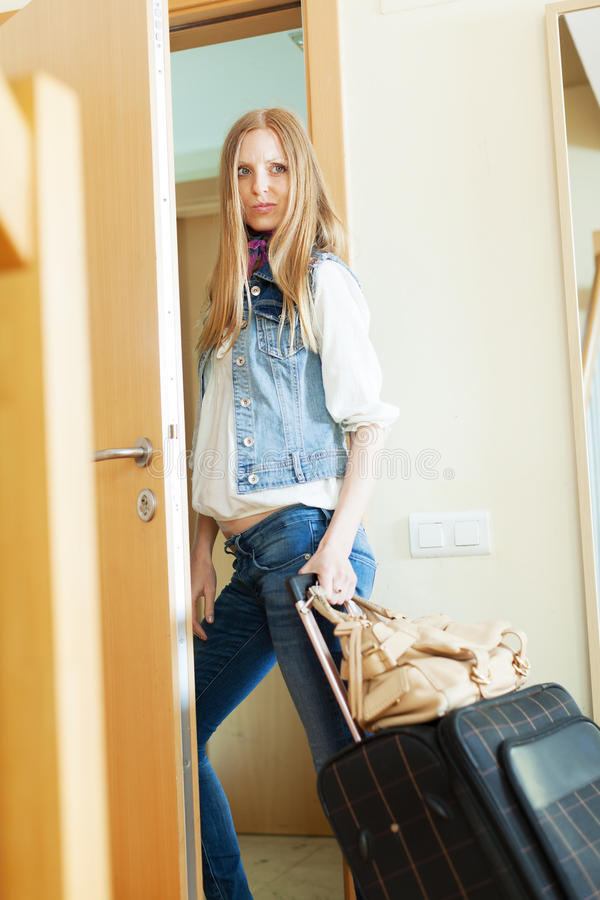 Λυπημένη γυναίκα με τις αποσκευές που αφήνει το σπίτι στοκ εικόνες