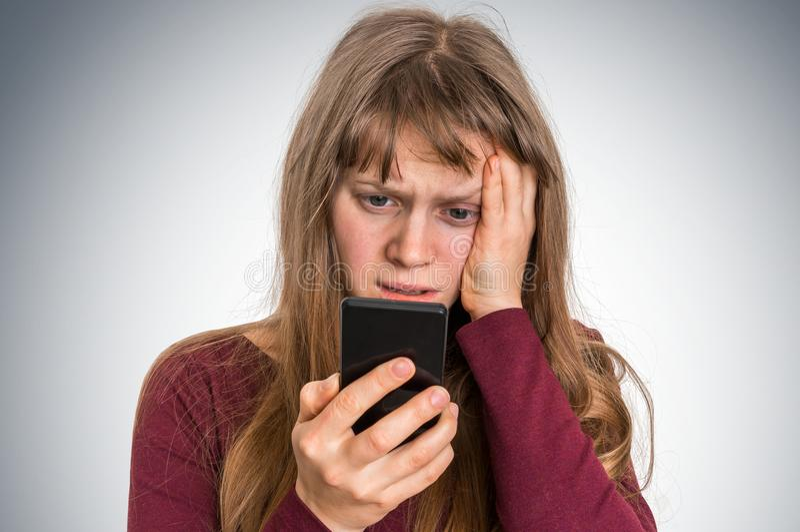 Λυπημένη γυναίκα με το κινητό τηλέφωνο - κακή έννοια ειδήσεων στοκ φωτογραφία