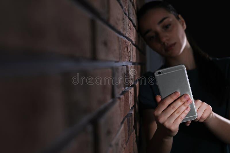 Λυπημένη γυναίκα με το κινητό τηλέφωνο κοντά στο τουβλότοιχο Έννοια μοναξιάς στοκ φωτογραφία με δικαίωμα ελεύθερης χρήσης
