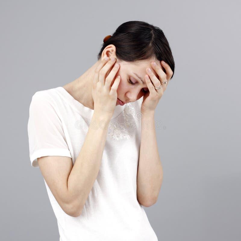 Λυπημένη γυναίκα που απομονώνεται στο γκρίζο υπόβαθρο στοκ φωτογραφίες