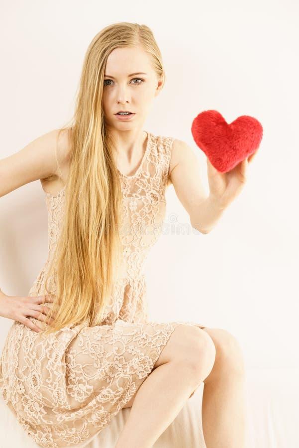 Λυπημένη γυναίκα που κρατά το κόκκινο μαξιλάρι στη μορφή καρδιών στοκ εικόνα