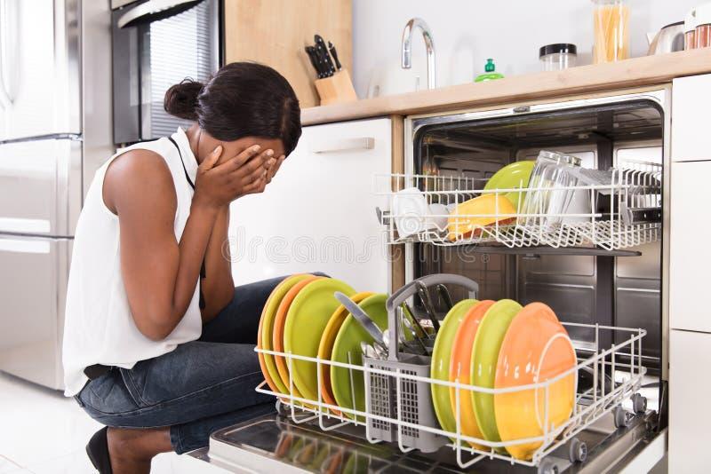 Λυπημένη γυναίκα που σκύβει κοντά στο πλυντήριο πιάτων στοκ φωτογραφίες με δικαίωμα ελεύθερης χρήσης