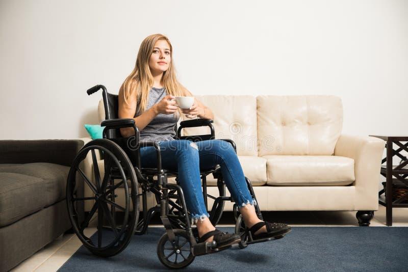Λυπημένη γυναίκα στην αναπηρική καρέκλα που χαλαρώνει στο σπίτι στοκ εικόνα
