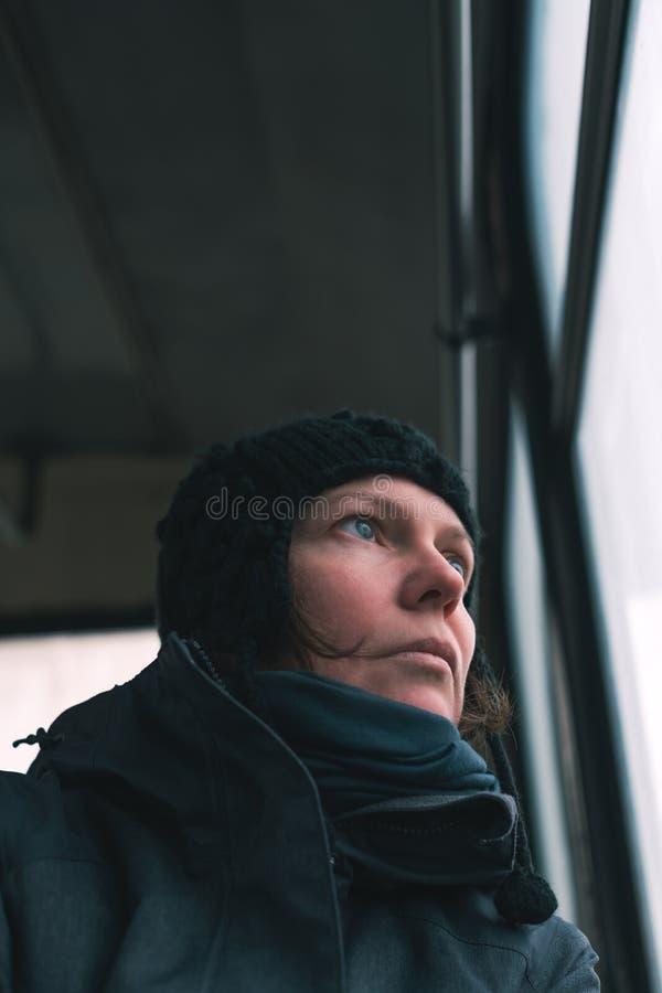 Λυπημένη γυναίκα στο λεωφορείο που κοιτάζει μέσω του παραθύρου στοκ εικόνες