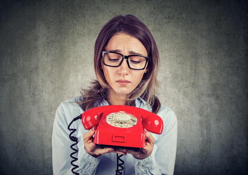 Λυπημένη επιχειρησιακή γυναίκα που περιμένει ένα τηλεφώνημα στοκ εικόνα