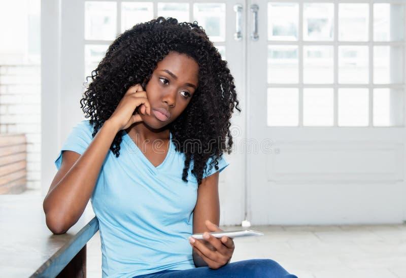 Λυπημένη και μόνη γυναίκα αφροαμερικάνων που περιμένει το μήνυμα στοκ φωτογραφία