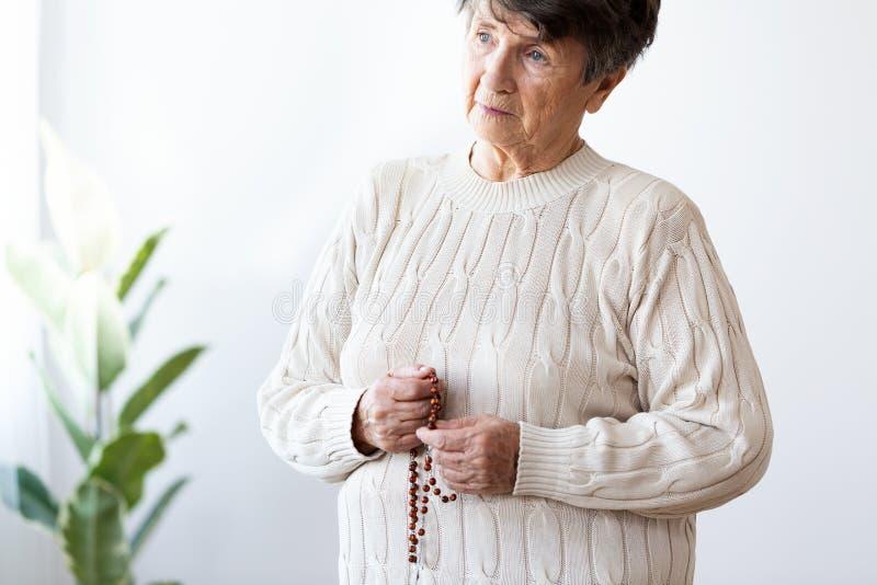 Λυπημένη και μόνη ηλικιωμένη γυναίκα που κρατά κόκκινο rosary με το σταυρό στοκ εικόνα