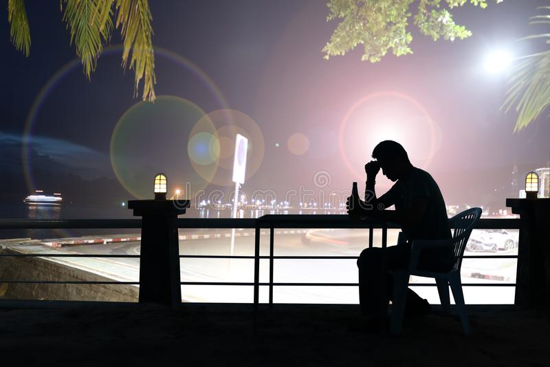 Λυπημένη μπύρα κατανάλωσης ατόμων σκιαγραφιών στο φραγμό, φω'τα νύχτας στοκ εικόνες με δικαίωμα ελεύθερης χρήσης