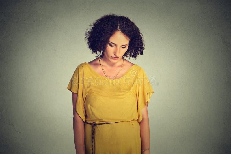 Λυπημένη μόνη νέα γυναίκα που κοιτάζει κάτω στοκ φωτογραφία