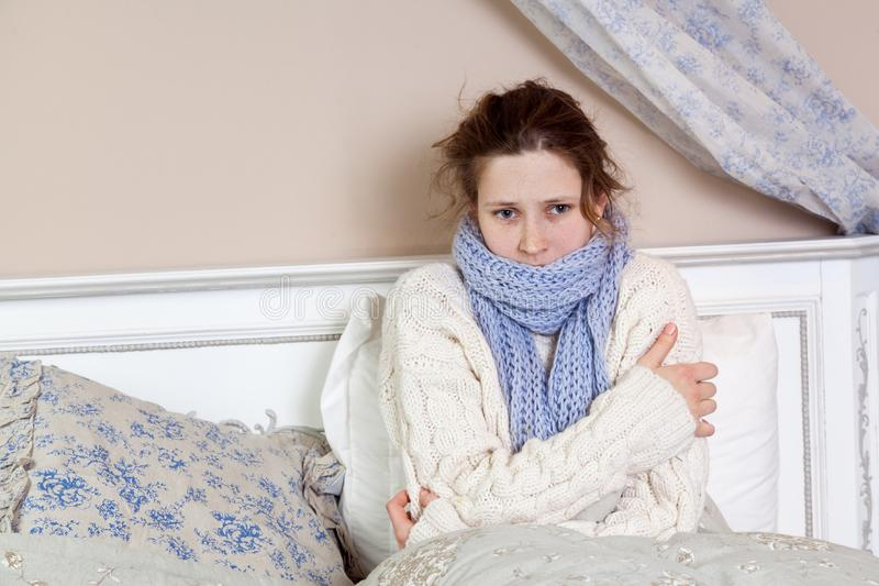 Λυπημένη μόνη νέα γυναίκα στο άσπρο πουλόβερ και το μπλε μαντίλι που αισθάνεται το κρύο άρρωστο και στηργμένος σπίτι στο κρεβάτι στοκ εικόνα με δικαίωμα ελεύθερης χρήσης