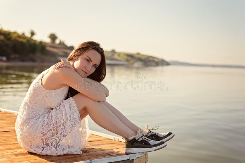 Λυπημένη μόνη νέα συνεδρίαση γυναικών που αγκαλιάζει τα γόνατά της στην αποβάθρα με τα λυπημένα μάτια, μοναξιά, χωρισμός, απάθεια στοκ εικόνες