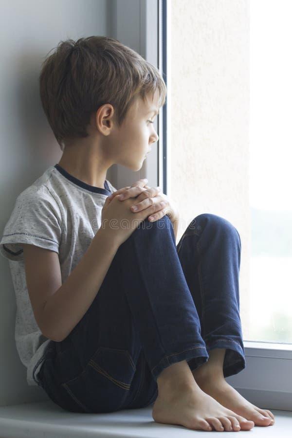 Λυπημένη μόνη συνεδρίαση παιδιών μόνο στο παράθυρο στο σπίτι στοκ φωτογραφίες