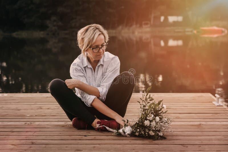 Λυπημένη μόνη όμορφη συνεδρίαση γυναικών στην αποβάθρα στοκ εικόνες