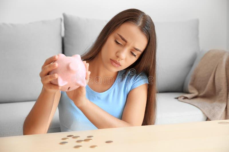Λυπημένη νέα γυναίκα με την κενή piggy τράπεζα στο σπίτι στοκ εικόνα με δικαίωμα ελεύθερης χρήσης
