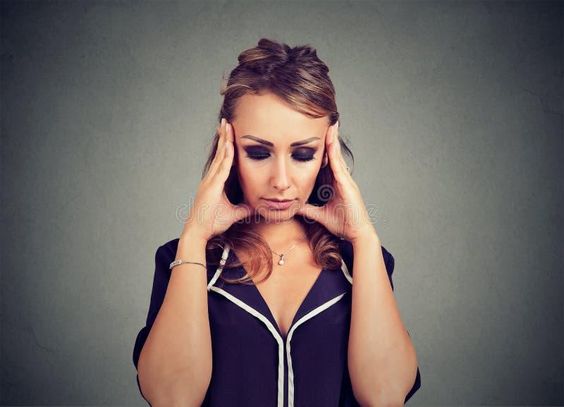 Λυπημένη νέα γυναίκα πορτρέτου κινηματογραφήσεων σε πρώτο πλάνο με την ανησυχημένη τονισμένη έκφραση προσώπου που κοιτάζει κάτω στοκ φωτογραφία