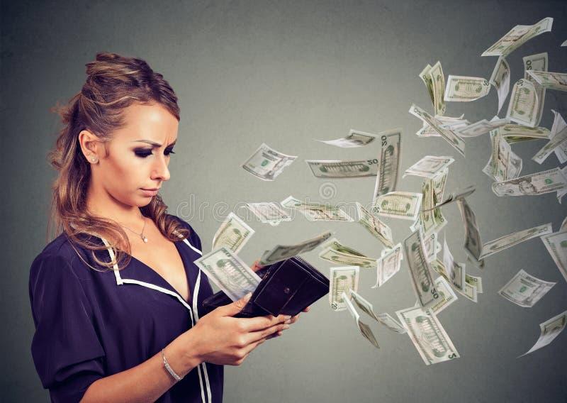 Λυπημένη νέα γυναίκα που εξετάζει το πορτοφόλι της με τα τραπεζογραμμάτια δολαρίων χρημάτων που πετούν έξω μακριά στοκ φωτογραφία