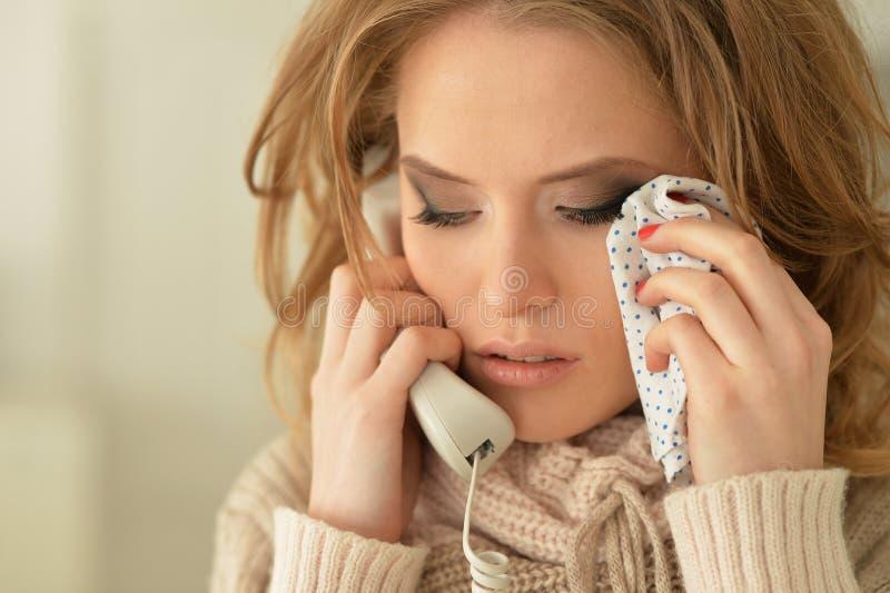 Λυπημένη νέα γυναίκα που μιλά στο τηλέφωνο και να φωνάξει στοκ εικόνες