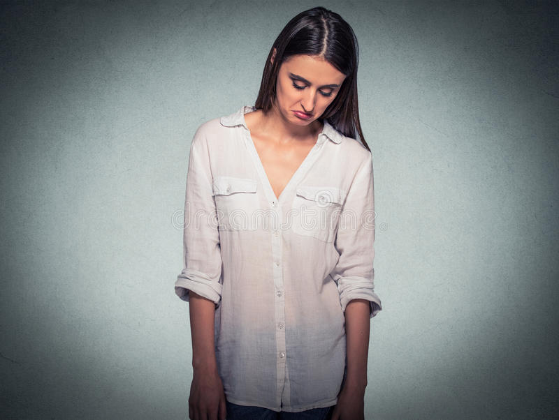 Λυπημένη ντροπαλή επισφαλής γυναίκα που κοιτάζει κάτω από την αποφυγή της οπτικής επαφής στοκ εικόνα