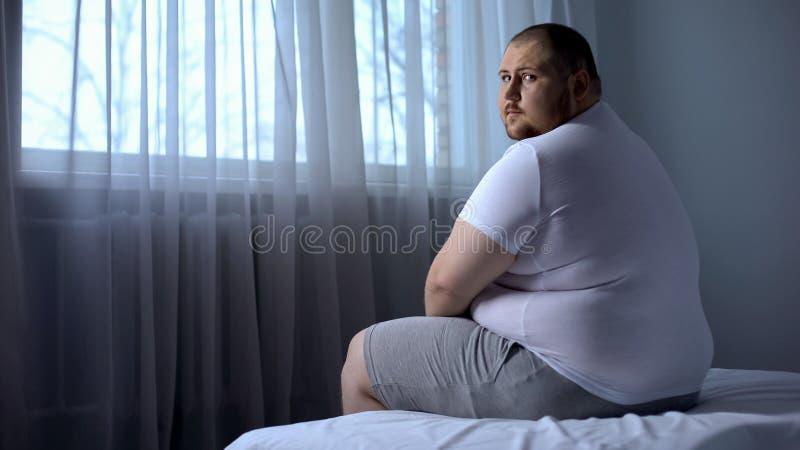 Λυπημένη παχιά συνεδρίαση ατόμων στο κρεβάτι στο σπίτι, που εξετάζει τη κάμερα, κατάθλιψη, αβεβαιότητες στοκ εικόνα