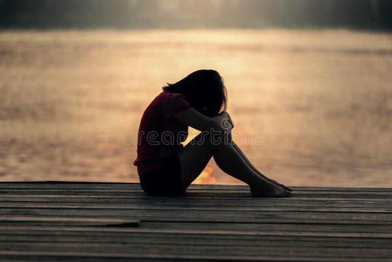 Λυπημένη σκιαγραφία γυναικών που ανησυχείται στο ηλιοβασίλεμα στοκ εικόνα με δικαίωμα ελεύθερης χρήσης