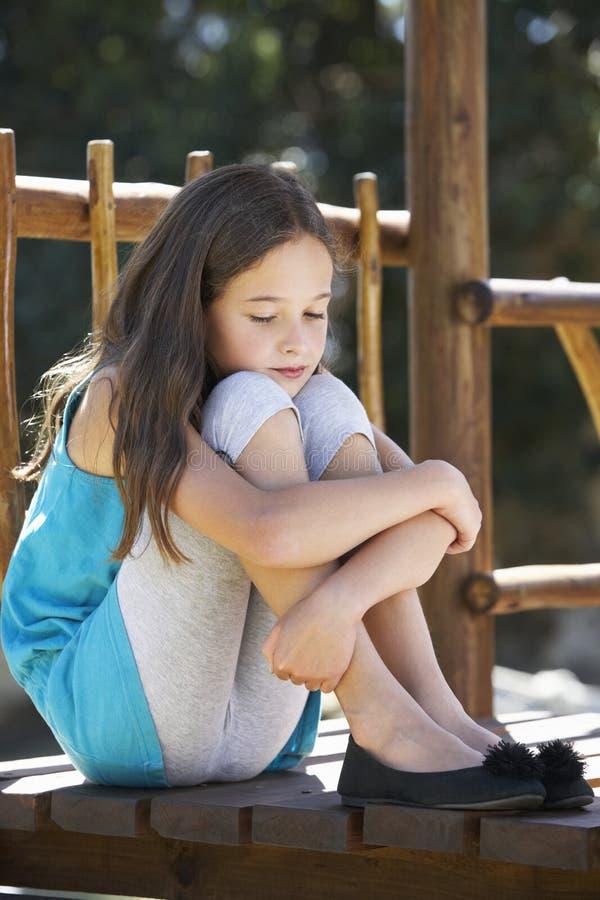 Λυπημένη συνεδρίαση νέων κοριτσιών στο πλαίσιο αναρρίχησης στοκ εικόνα με δικαίωμα ελεύθερης χρήσης
