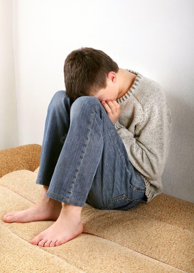 Λυπημένος έφηβος στον καναπέ στοκ φωτογραφία με δικαίωμα ελεύθερης χρήσης
