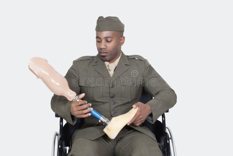 Λυπημένος αμερικανικός στρατιωτικός αξιωματούχος στην αναπηρική καρέκλα πόδι προσθέσεων εκμετάλλευσης πέρα από το γκρίζο υπόβαθρο στοκ εικόνες