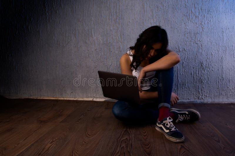 Λυπημένος και φοβησμένος θηλυκός έφηβος με το lap-top υπολογιστών που υφίσταται και την παρενόχληση που είναι σε απευθείας σύνδεσ στοκ φωτογραφίες