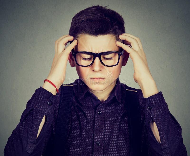 Λυπημένος νεαρός άνδρας με την ανησυχημένη τονισμένη έκφραση προσώπου που κοιτάζει κάτω στοκ εικόνες