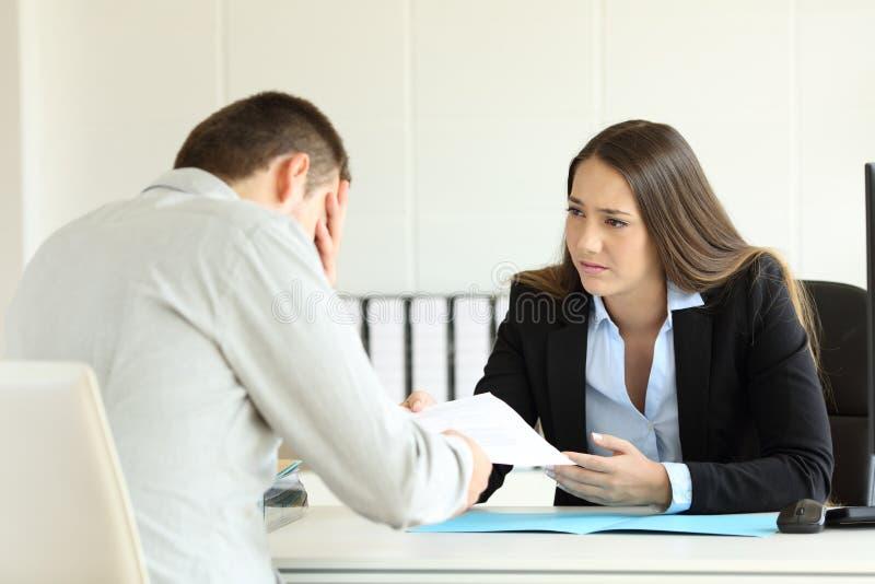 Λυπημένος προϊστάμενος που απολύει έναν υπάλληλο στο γραφείο στοκ φωτογραφίες