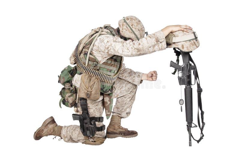 Λυπημένος στρατιώτης που γονατίζει λόγω του θανάτου φίλων στοκ φωτογραφία με δικαίωμα ελεύθερης χρήσης