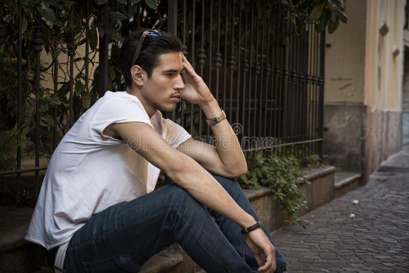 Λυπημένος, δυστυχισμένος νεαρός άνδρας υπαίθριος, καθμένος στο πεζοδρόμιο στοκ εικόνες με δικαίωμα ελεύθερης χρήσης