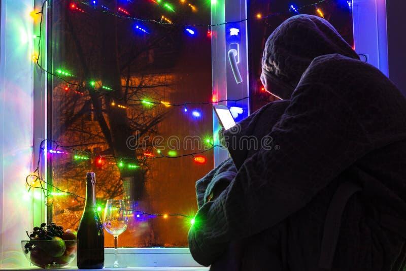 λυπημένο άτομο σε μια κουκούλα με ένα smartphone θολωμένο bokeh, στο υπόβαθρο του παραθύρου που διακοσμείται με τις γιρλάντες με  στοκ φωτογραφίες με δικαίωμα ελεύθερης χρήσης