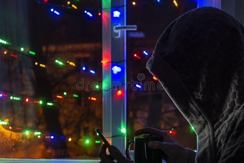 λυπημένο άτομο σε μια κουκούλα με ένα smartphone θολωμένο bokeh, στο υπόβαθρο του παραθύρου που διακοσμείται με τις γιρλάντες με  στοκ φωτογραφία