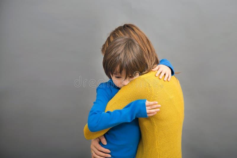 Λυπημένο λίγο παιδί, αγόρι, που αγκαλιάζει τη μητέρα του στο σπίτι, απομόνωσε imag στοκ εικόνες